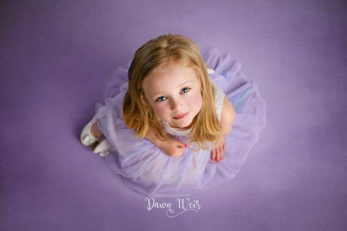 edmonton child photographer dawn weir 4 year old girl looking up while sitting wearing purple dress