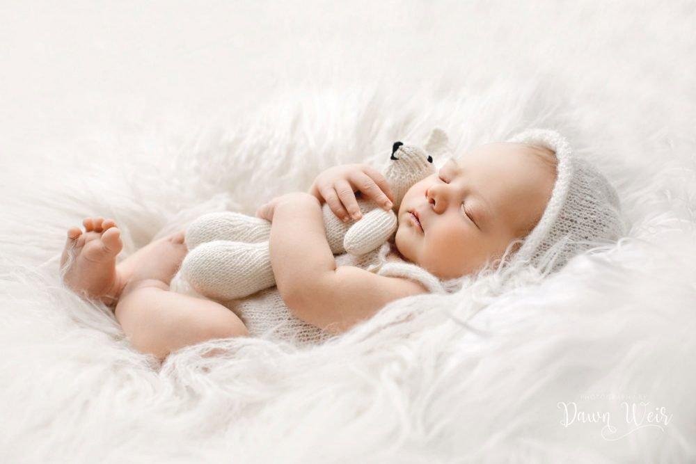 newborn photography edmonton baby lying in white fur with teddy