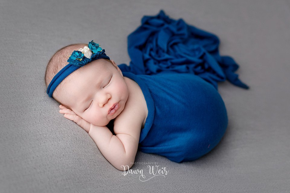 photo-by-newborn-photographer-dawn-weir-blue-flower-headband-baby-lying-on-grey-blanket