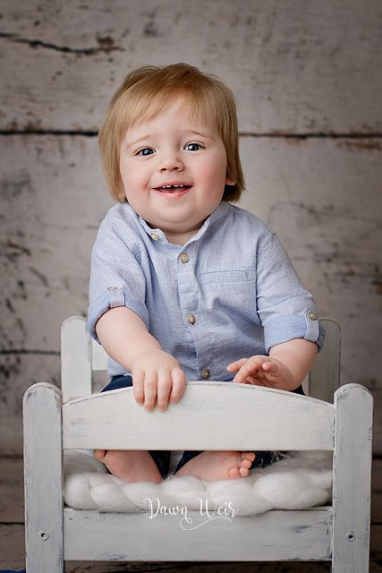 photo by dawn weir first birthday photography session boy on white bed with wood background blue shirt and jeans