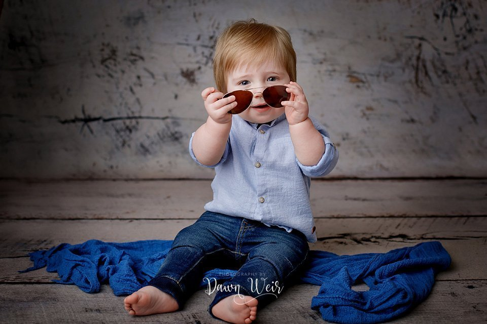 photo by dawn weir first birthday photography session boy on wood background blue shirt and jeans