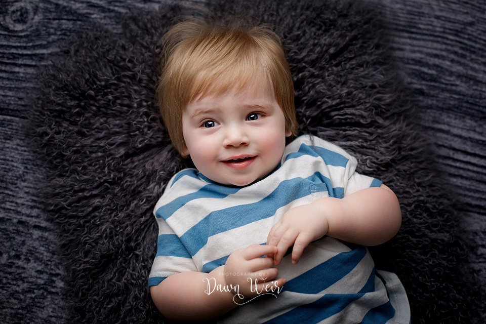 photo by dawn weir first birthday photography session boy grey background and a blue and white striped shirt