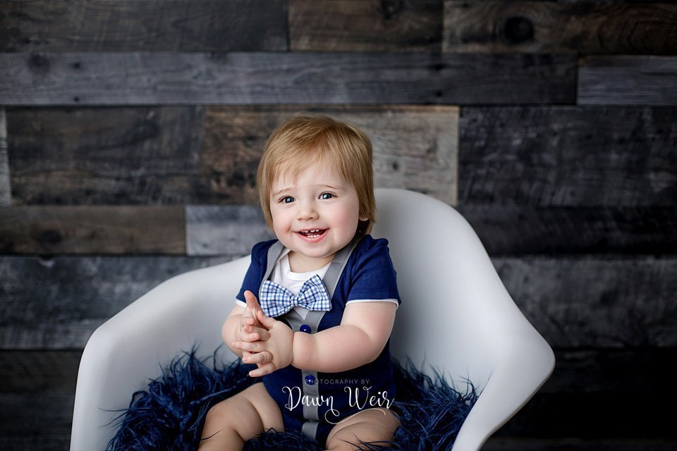photo by dawn weir first birthday photography session boy grey wood background blue romper with bow tie and buttons on white chair