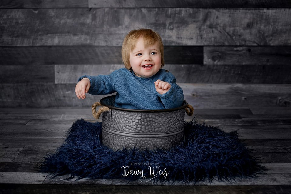 photo by dawn weir first birthday photography session boy grey wood background blue sweater sitting in tin bucket