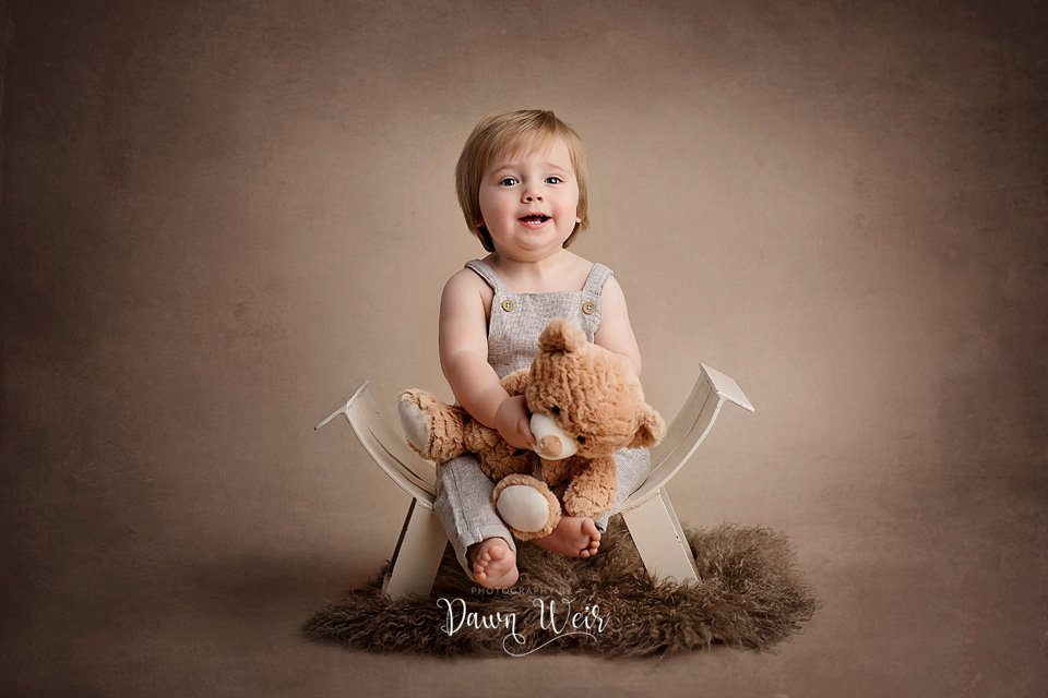 photo by dawn weir first birthday photography session boy in romper on brown fur and neutral tones