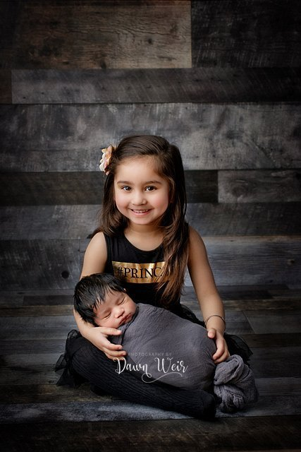 photo by photography by dawn weir newborn boy with big sister sitting wood backdrop
