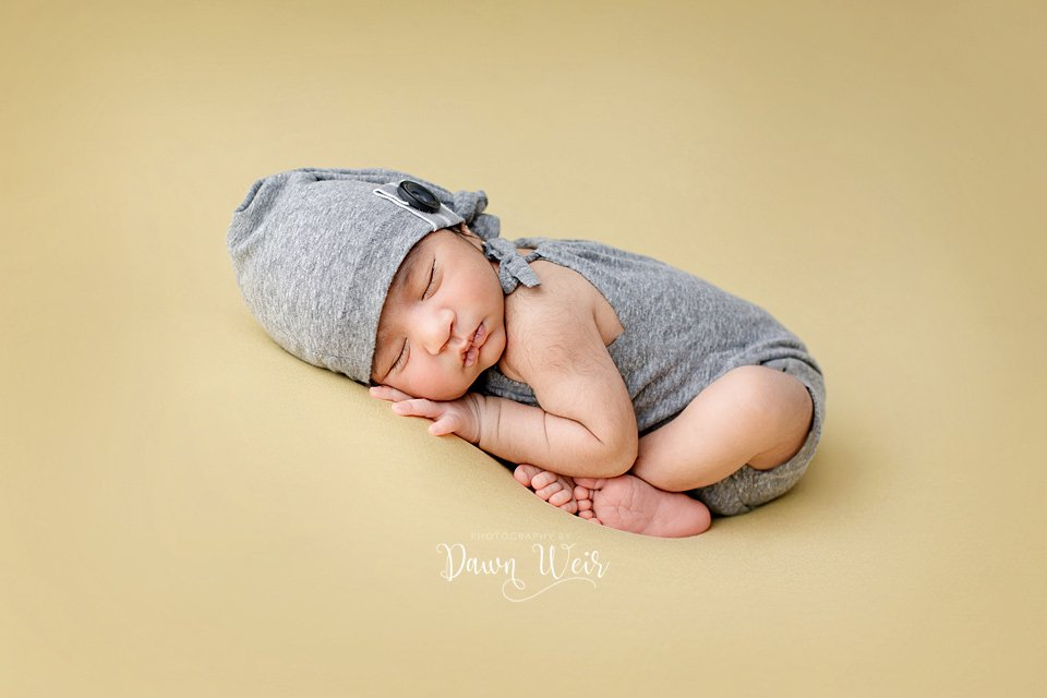 photo by photography by dawn weir newborn boy in a grey romper and hat on yellow blanket lying