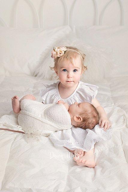 edmonton newborn photographer dawn weir sister toddler holding newborn baby white background