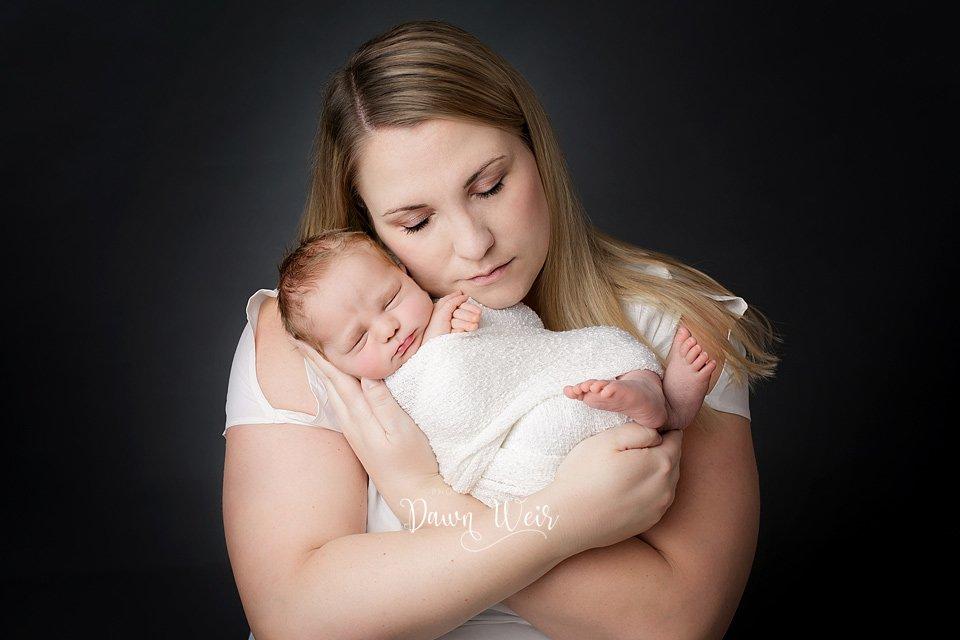 edmonton newborn photographer dawn weir mom holding baby wearing white grey background