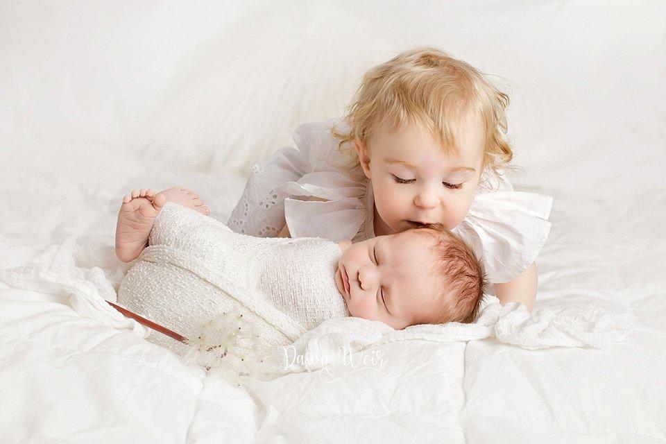 edmonton newborn photographer dawn weir toddler girl kissing baby all white