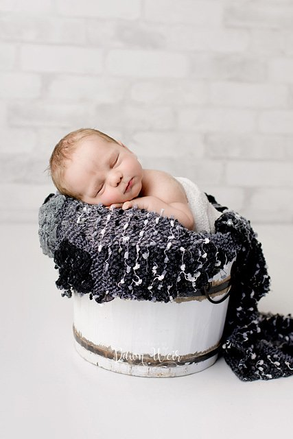 edmonton newborn photographer dawn weir newborn baby in wood bucket with grey and black accents