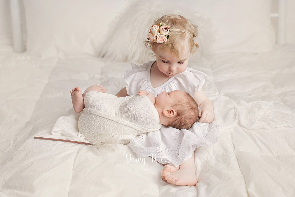 edmonton newborn photographer dawn weir little girl with newborn baby in white