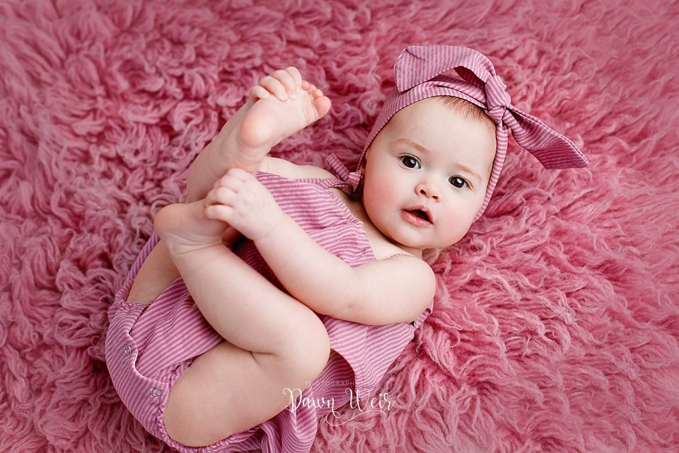 by dawn weir 6 month old baby girl photo session pink flokati rug baby on back looking up