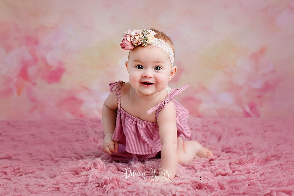 by dawn weir 6 month old baby girl photo session pink flokati rug with baby on hands and knees smiling