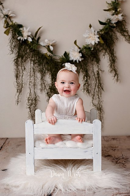 by dawn weir 6 month old baby girl photo session in white romper with hanging flowers in background sitting on bed smiling