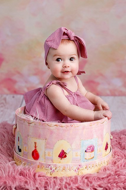 by dawn weir 6 month old baby girl photo session pink flokati rug with baby in pink bucket smiling