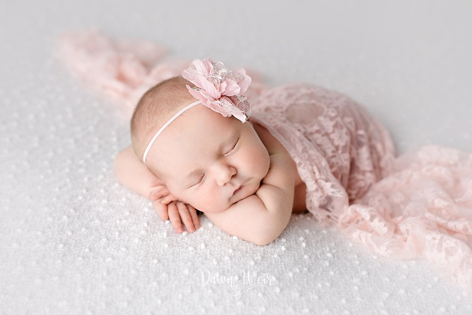 photo by dawn weir newborn girl lying on hands on white blanket covered in pink lace