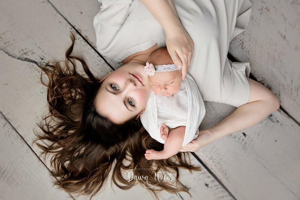 photo by dawn weir mom holding newborn baby girl wood backdrop lying on floor on back