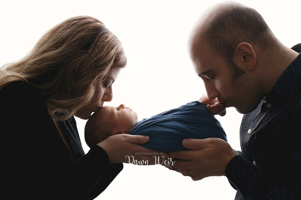 photo by dawn weir edmonton newborn boy blue wrap white background mom and dad kissing baby