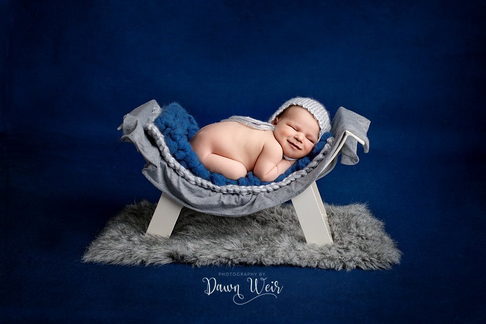 photo by dawn weir edmonton newborn boy blue on bed smiling grey fur