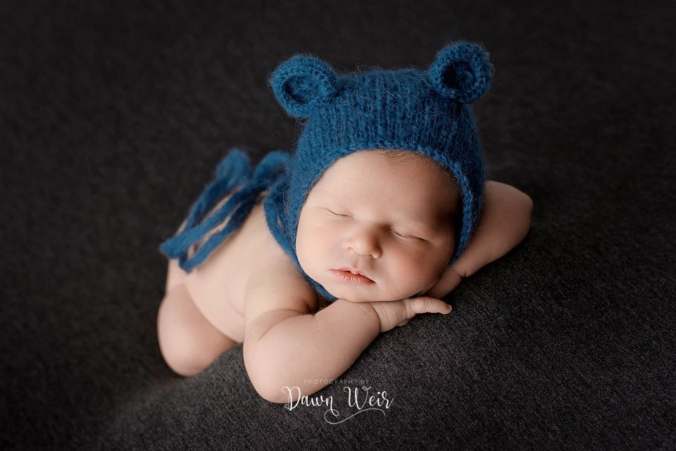 photo by dawn weir edmonton newborn boy on grey blanket lying on hands with blue bear hat