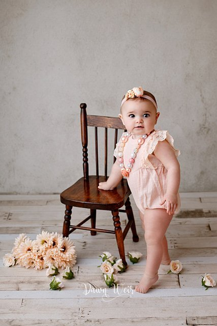 edmonton cake smash photographer dawn weir peach romper on a one year old girl standing by chair with peach flowers around