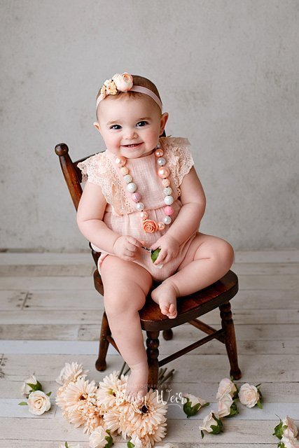 edmonton cake smash photographer dawn weir peach romper on a one year old girl sitting by chair with peach flowers around