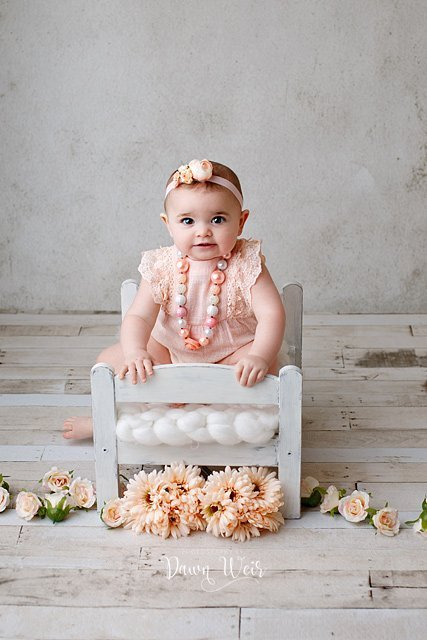 edmonton cake smash photographer dawn weir peach romper on a one year old girl sitting in a bed with peach flowers around