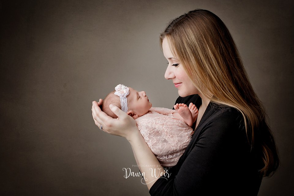edmonton newborn photographer dawn weir mom holding baby and looking at her