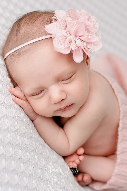 edmonton newborn photographer dawn weir baby girl lying on white blanket