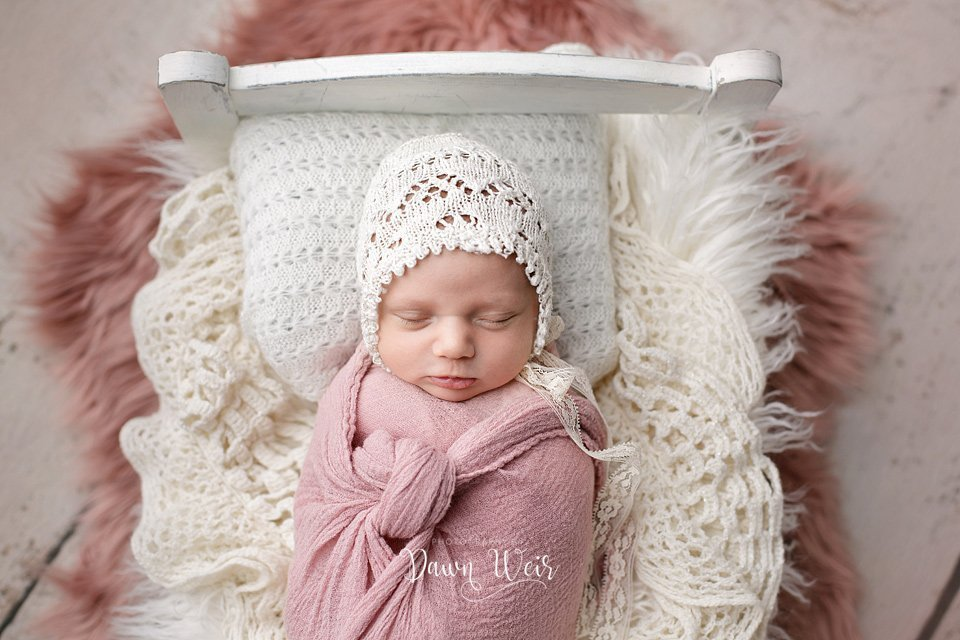 edmonton newborn photographer dawn weir pink accents in bed baby girl