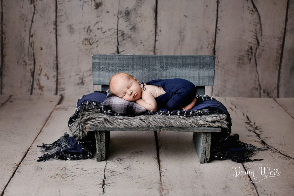newborn photography grey wood bench with newborn lying on it