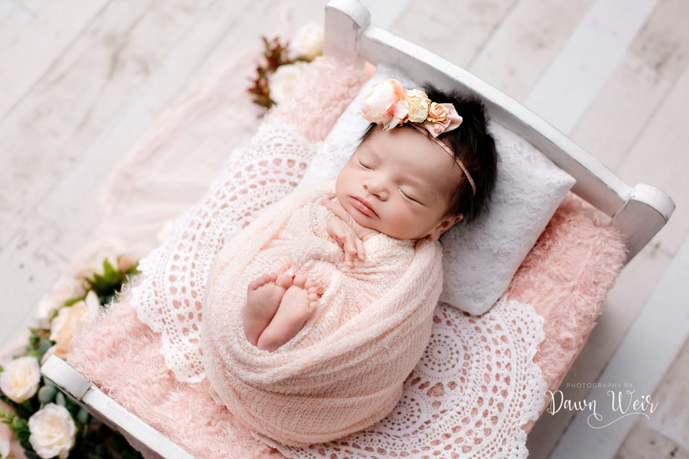 newborn photography with baby wrapped in peach lying in bed with white lace