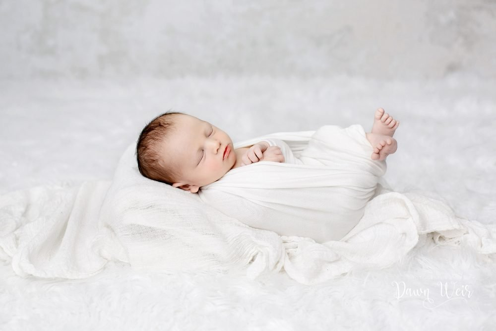 all white newborn wrapped in white lying on the white fur