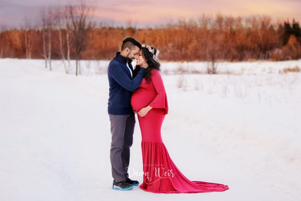 maternity photo session outside winter snow wearing red gown sunset
