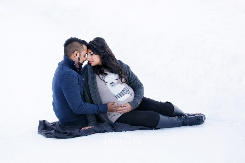 maternity photo session lady lying on blanket in snow looking at belly
