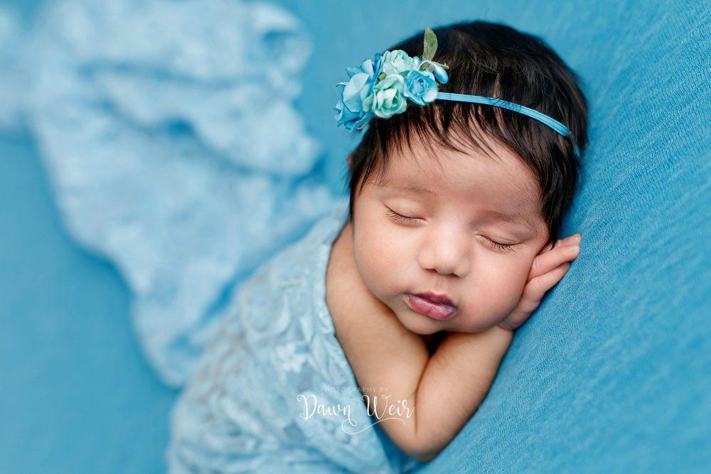 newborn girl lying on sky blue blanket