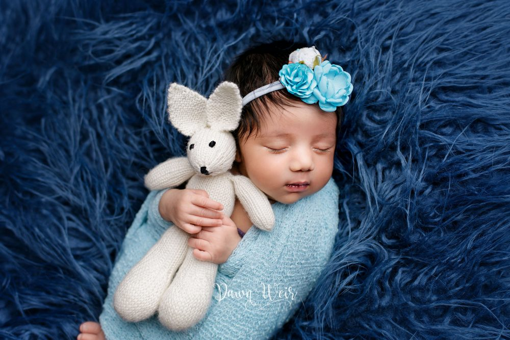 newborn baby girl lying on blue fur holding teddy bear