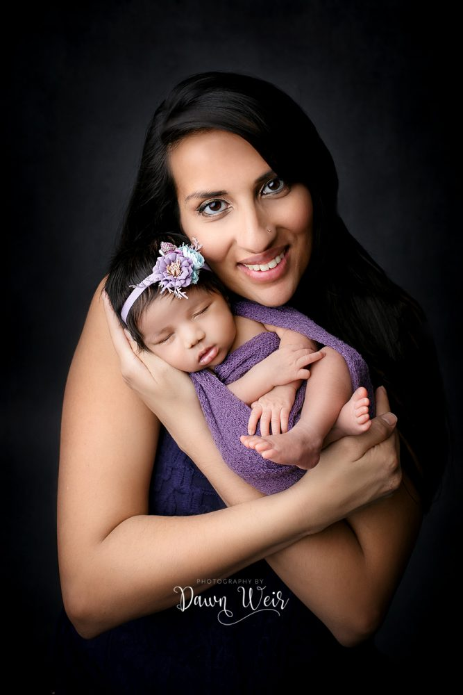 mom holding newborn girl looking at camera