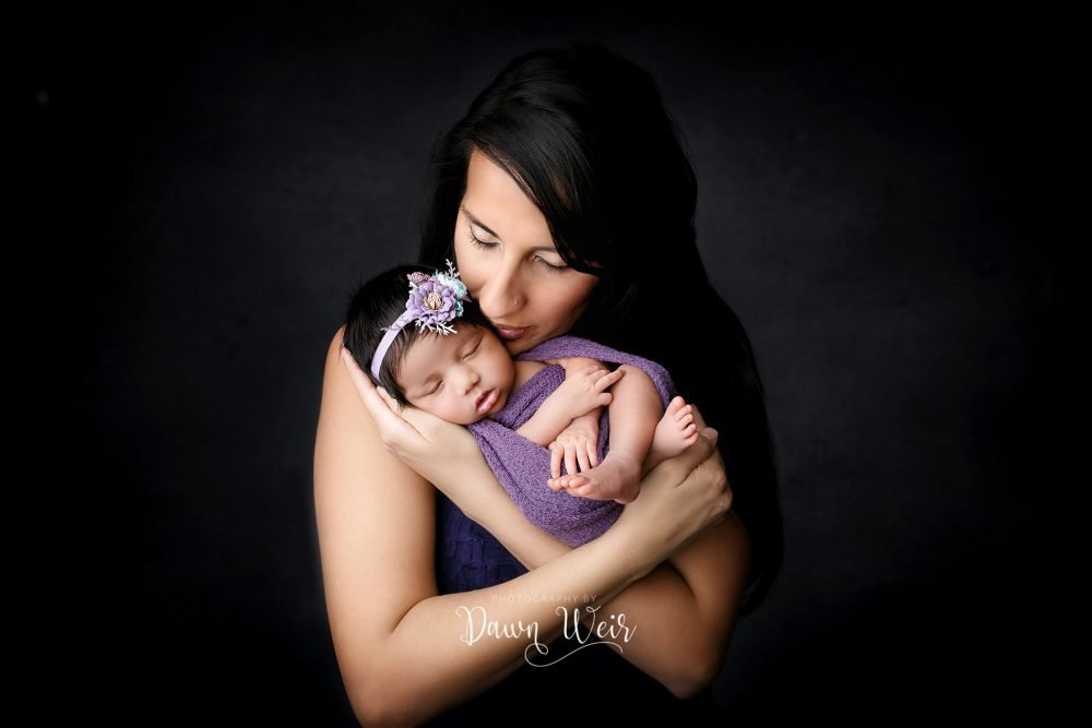 mother kissing newborn girl wearing purple