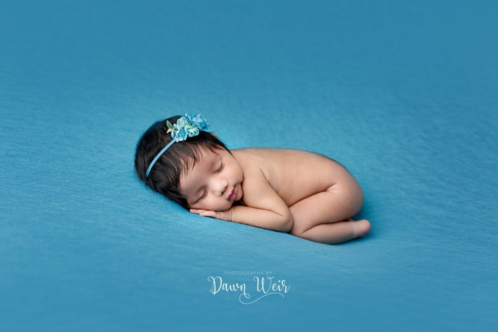 newborn girl lying on sky blue blanket