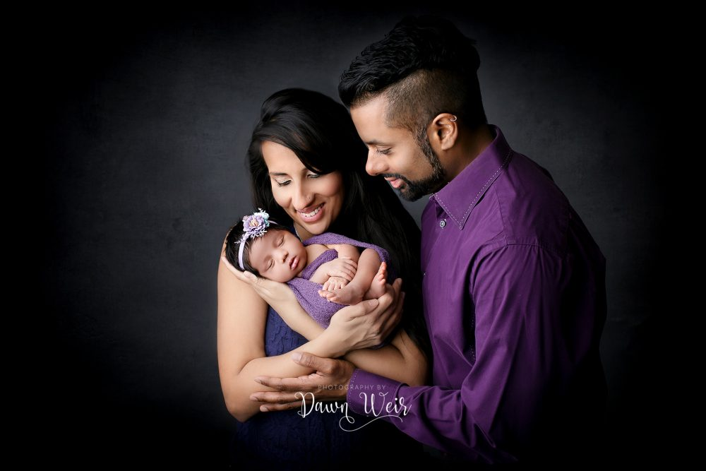 Mom and Dad looking at newborn baby wearing purple on black backdrop