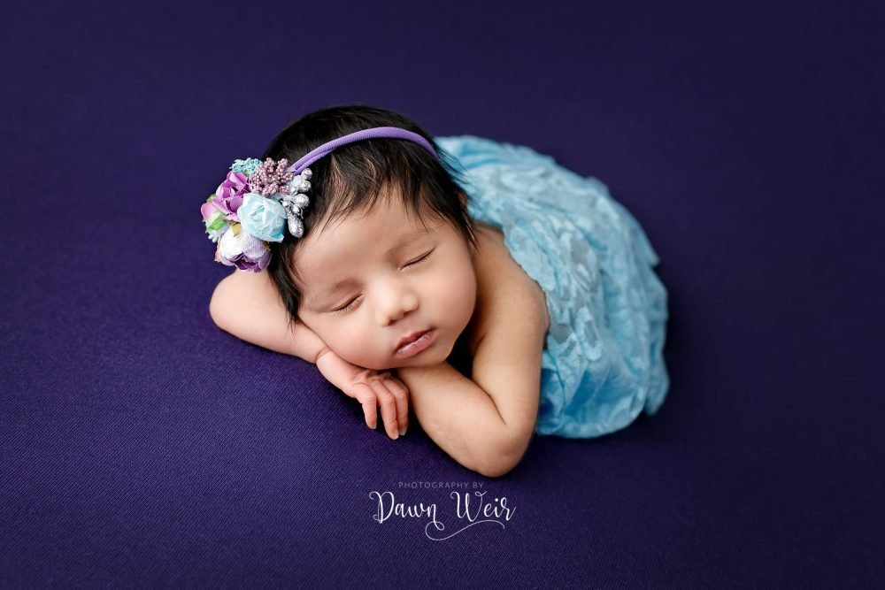 newborn girl lying on dark purple blanket with blue and purple accents flowers and wraps
